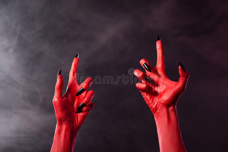 有黑锋利的钉子的蠕动的红魔手 库存照片