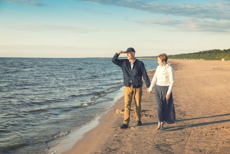 有年长的夫妇在海滩的浪漫步行 图库摄影