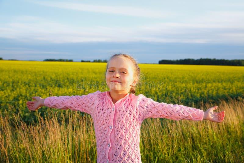 有延长的胳膊的一个小女孩在油菜领域前面 图库摄影