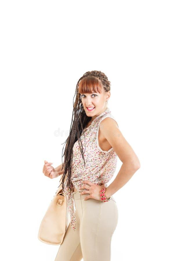 有延长的辫子头发的妇女在紧的棕色裤子和衬衣 库存照片