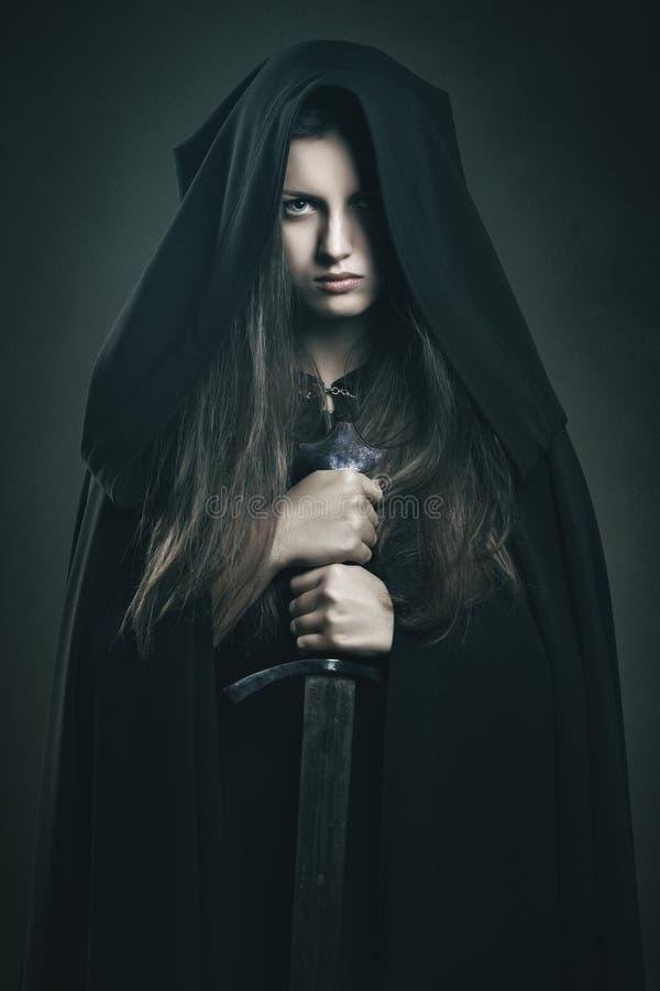 有黑长袍和剑的美丽的黑暗的妇女 免版税库存图片