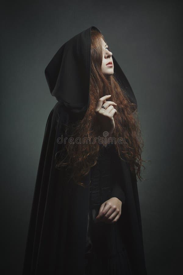 有黑长袍的美丽的红发妇女 免版税库存照片