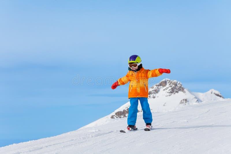 有滑雪帽和胳膊单独的滑雪的男孩在冬天 免版税库存图片