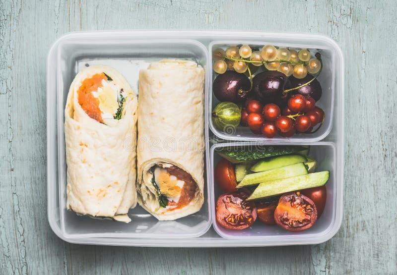 有素食玉米粉薄烙饼套、切好的蔬菜和水果的健康午餐盒在木背景 库存照片