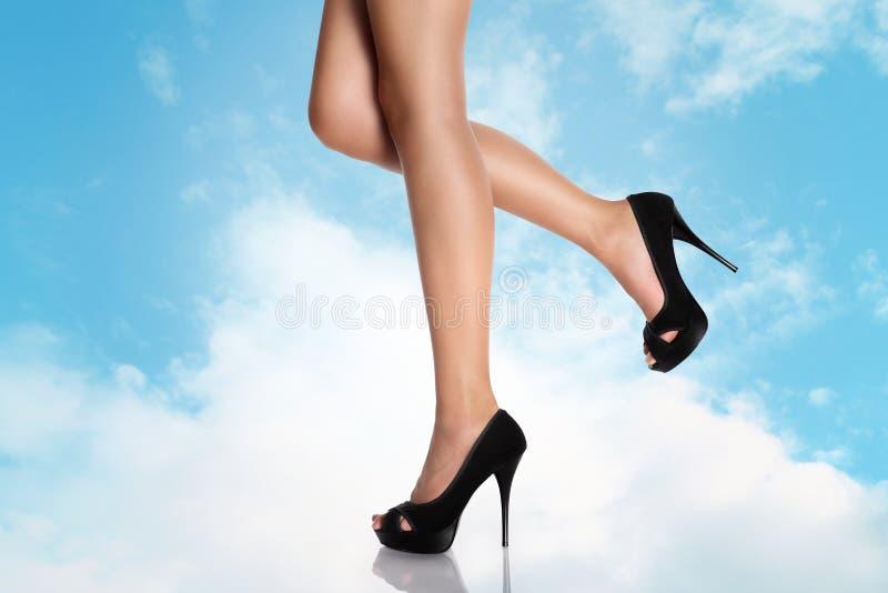 有黑高跟鞋的腿在天空 库存图片