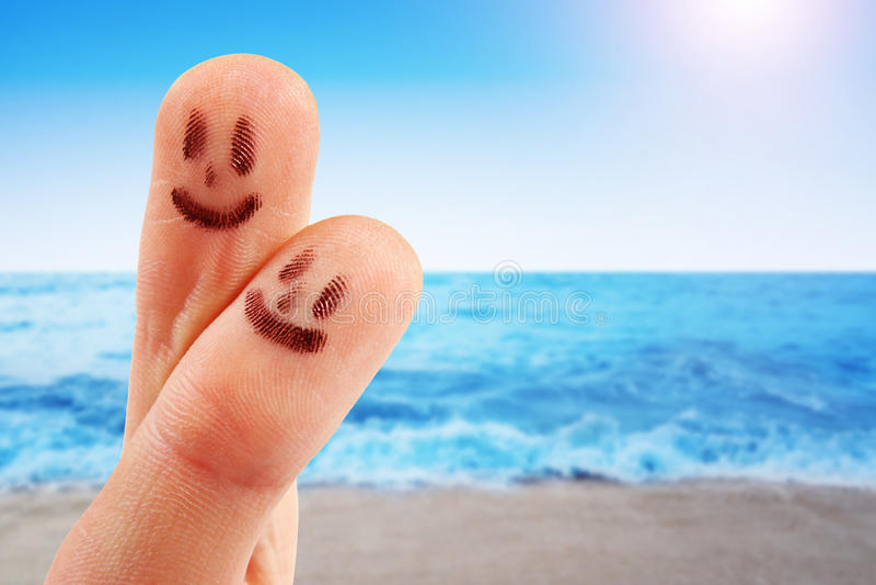 有兴高采烈的面孔的指尖在海滩 库存图片