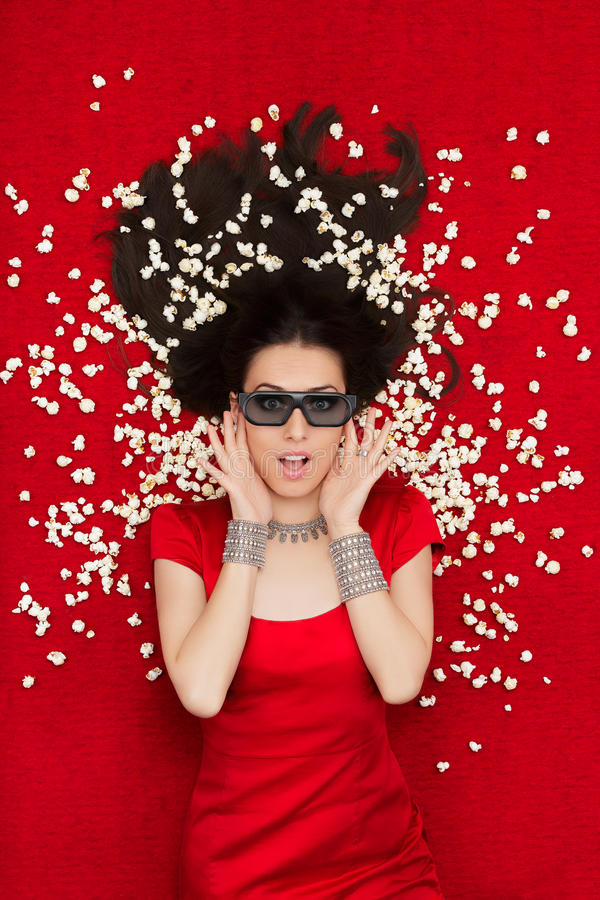 有3D戏院玻璃和玉米花的惊奇的女孩观看电影的 库存图片