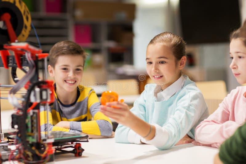 有3d打印机的愉快的孩子在机器人学学校 免版税库存图片