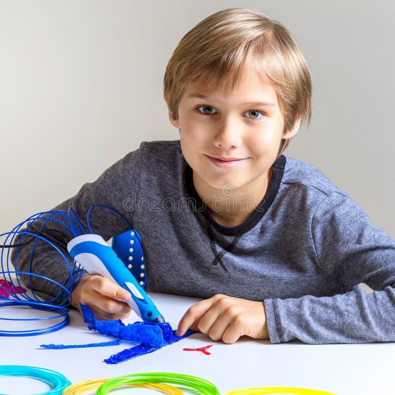 有3d打印笔的微笑的男孩 免版税库存照片