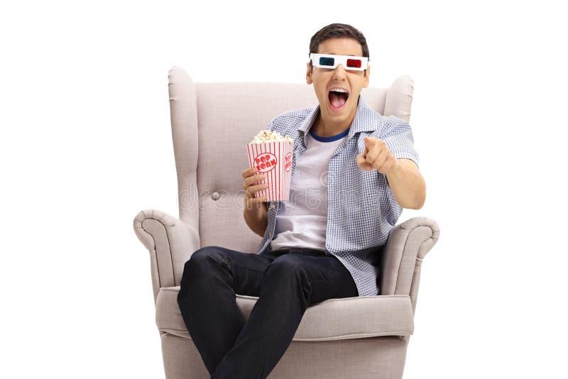 有3D玻璃和玉米花的人在扶手椅子笑和指向照相机的 库存照片