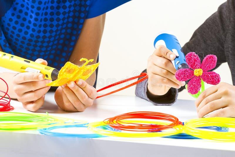 有3d笔的孩子手和在白色桌上的五颜六色的细丝 库存照片