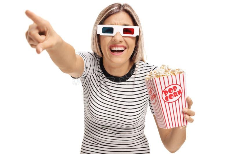 有3D玻璃和玉米花的笑的少妇指向和 免版税库存照片