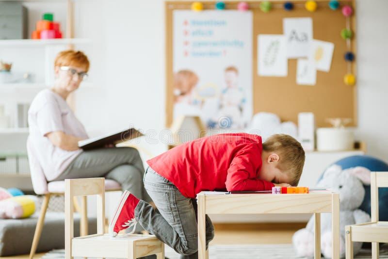 有ADHD的逗人喜爱的小男孩在与专业治疗师的会议期间 免版税库存照片