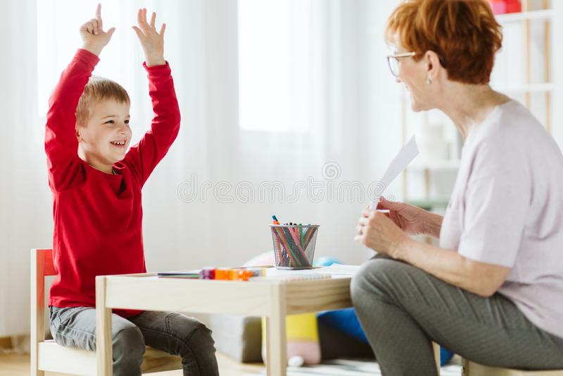 有ADHD的逗人喜爱的男孩在与专业治疗师的会议期间 免版税库存照片