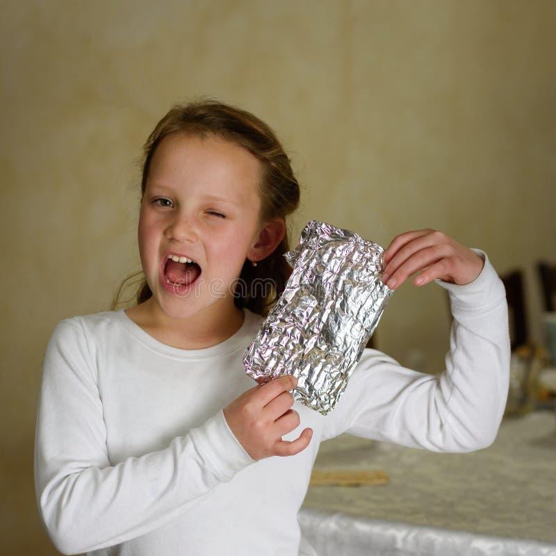 有Afikoman的女孩是残破的逾越节Seder matzah的一个半片断  免版税库存照片