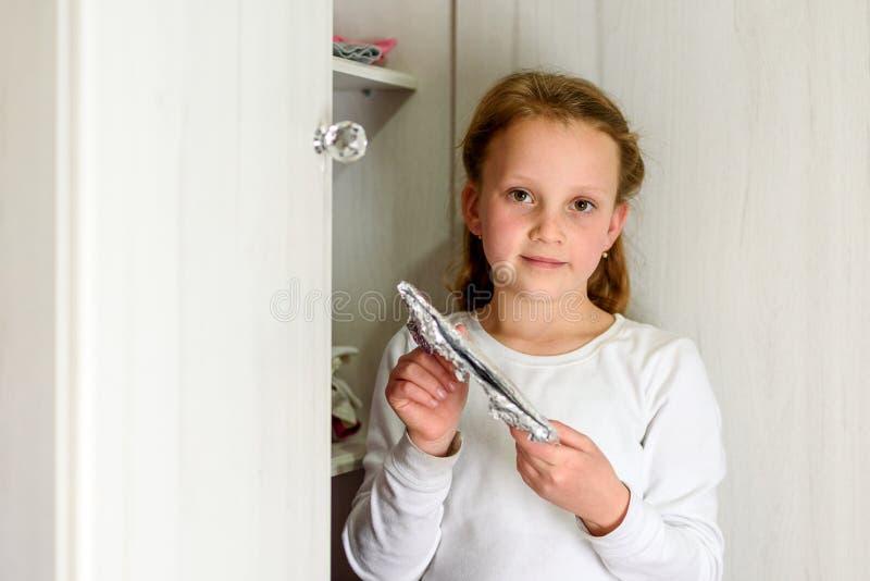 有Afikoman的女孩是残破的逾越节Seder matzah的半片断  免版税库存照片