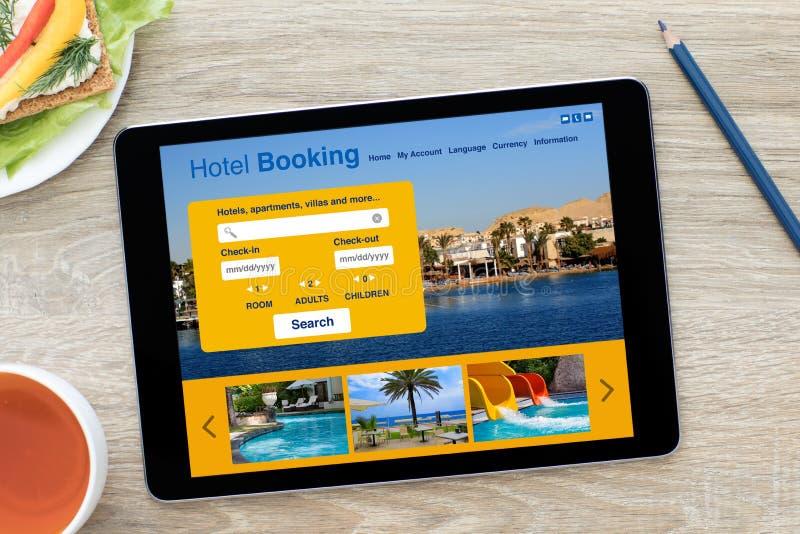 有app旅馆预定屏幕的计算机片剂在木桌上 免版税库存照片