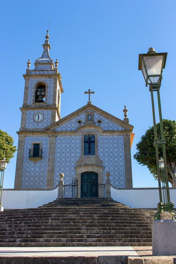 有azulejo瓦片的美丽的教会在好日子在葡萄牙 有响铃、十字架、时钟和街灯的宽容大教堂 库存图片