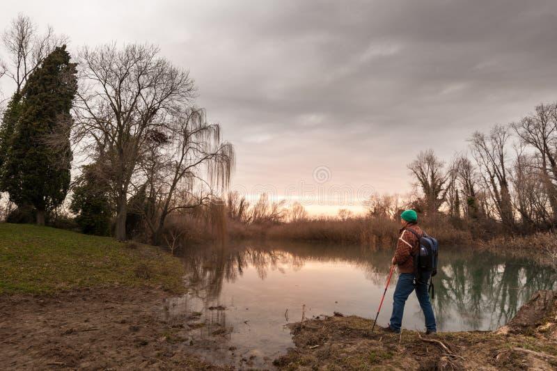 有backpakck的远足者在河岸 免版税库存图片