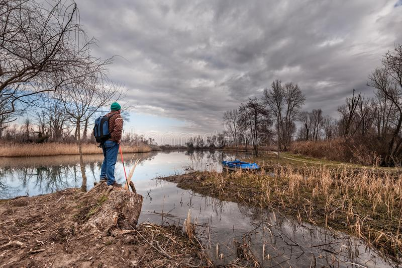 有backpakck的远足者在河岸 免版税库存照片