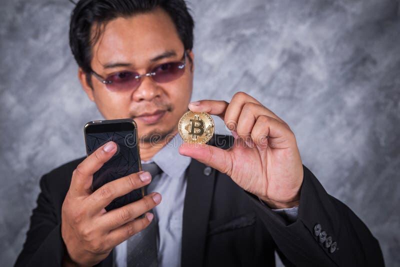 有bitcoin和使用的手机商人 免版税图库摄影