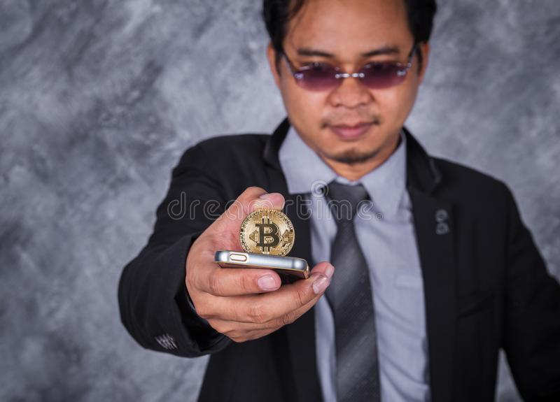 有bitcoin和使用的手机商人 库存图片