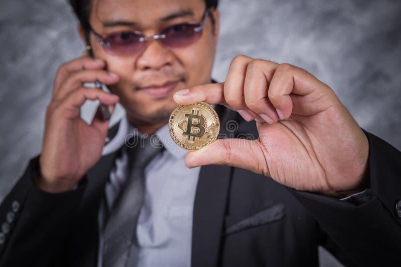 有bitcoin和使用的手机商人 库存照片