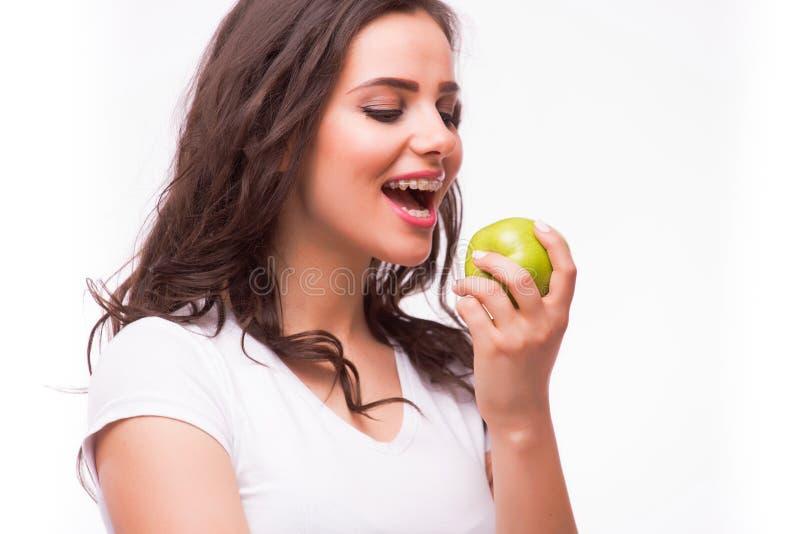有brances的女孩吃苹果 有牙齿括号和苹果的女性牙 免版税库存图片