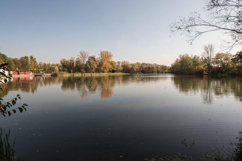 有buidling的池塘在银行的Lodenice,在公园Bozeny Nemcove的五颜六色的树在捷克共和国的卡尔维纳市在秋天期间 库存图片