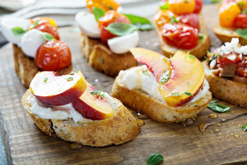 有caprese,蕃茄和桃子的Crostini或bruschetta委员会 库存照片