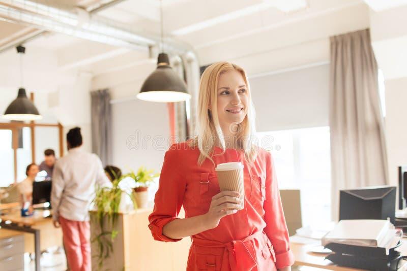 有coffe杯子的愉快的创造性的女性办公室工作者 库存图片