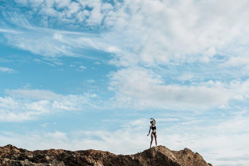 有dreadlocks在内衣和被刺字的立场的一名妇女在距离的含沙小山 与云彩的天空蔚蓝,拷贝 免版税库存图片