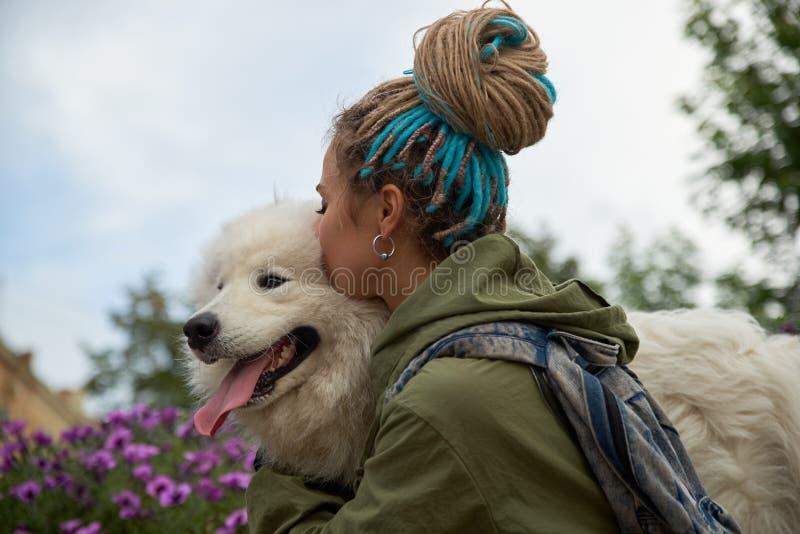 有dreadlocks的现代时髦的女孩在她的头拥抱并且亲吻她心爱的狗雪白萨莫耶特人 免版税图库摄影