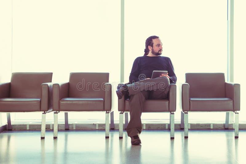 有dreadlocks的英俊的年轻人使用他的在机场休息室的数字式片剂个人计算机,现代候诊室,有背后照明的 免版税库存图片