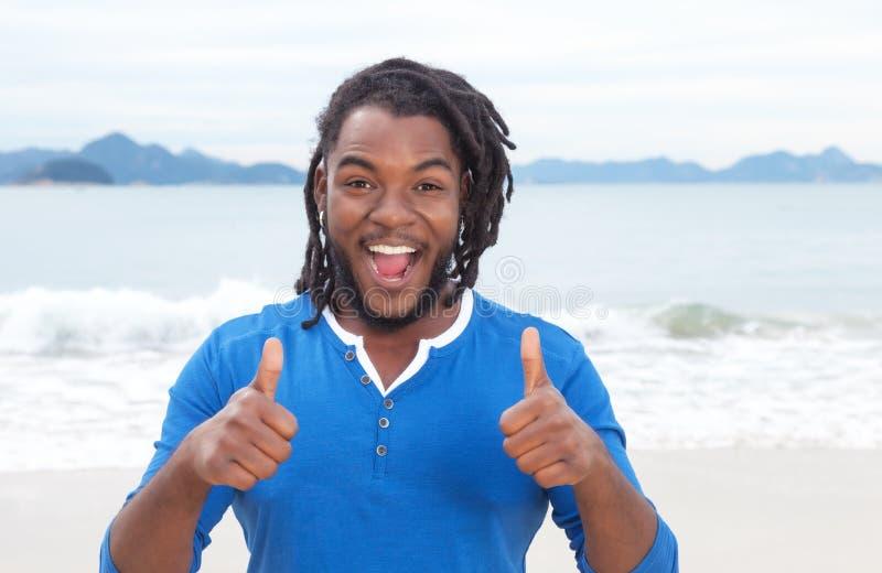 有dreadlocks的非裔美国人的人在显示两个拇指的海滩 免版税库存图片