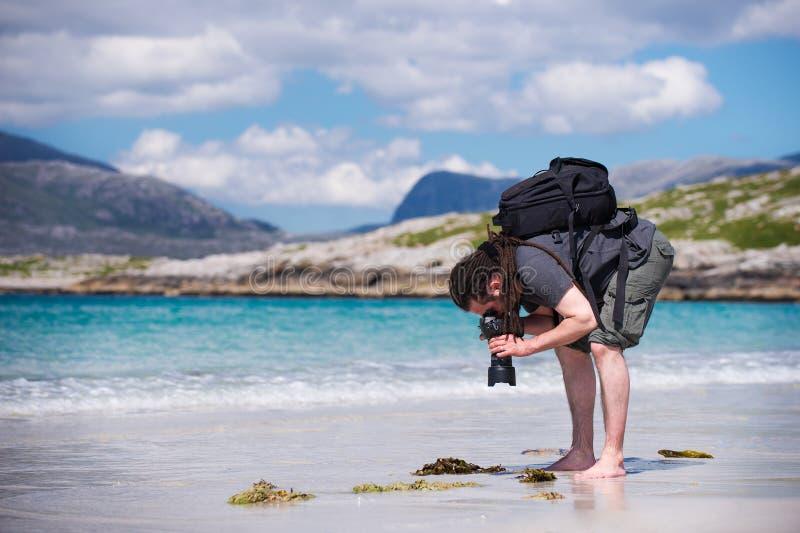 有dreadlocks的年轻男性摄影师在一个晴朗的白色沙子海滩, Luskentyre,哈里斯, Hebrides,苏格兰小岛  免版税库存图片