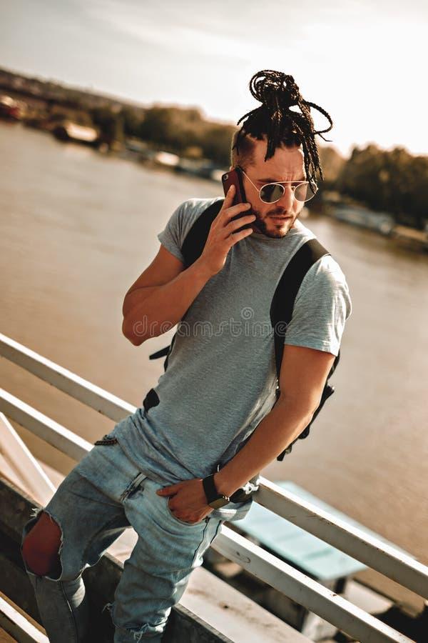 有dreadlocks谈话的人恼怒在电话由河 免版税库存图片
