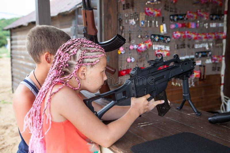 有dreds射击的女孩与在靶场的枪,兄弟支持的边 图库摄影