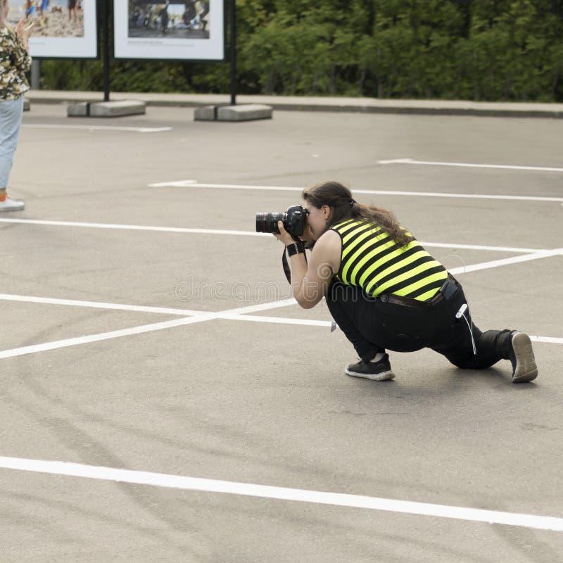 有DSLR照相机的一位女性摄影师秘密地拍照片 库存图片