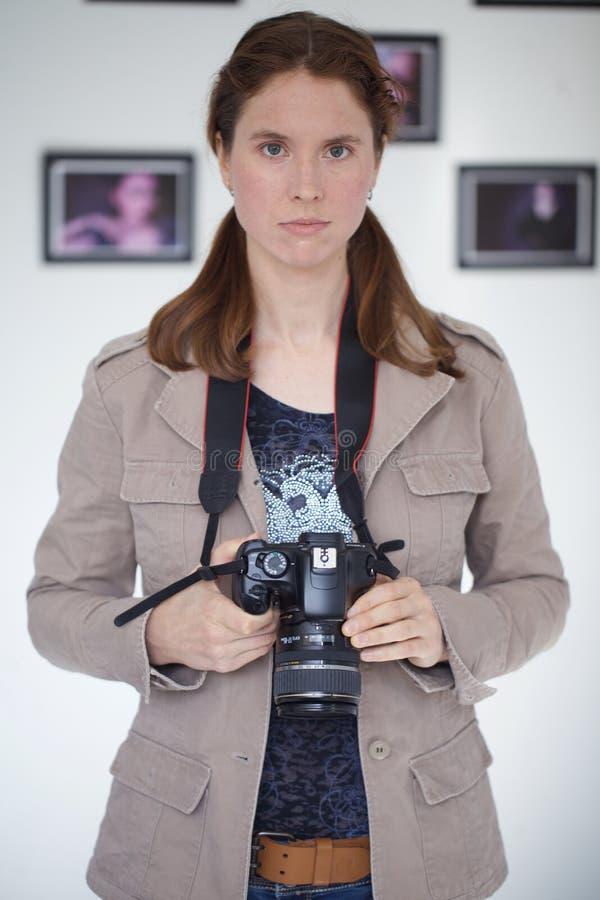 有DSLR照相机的年轻俏丽的妇女 免版税库存照片