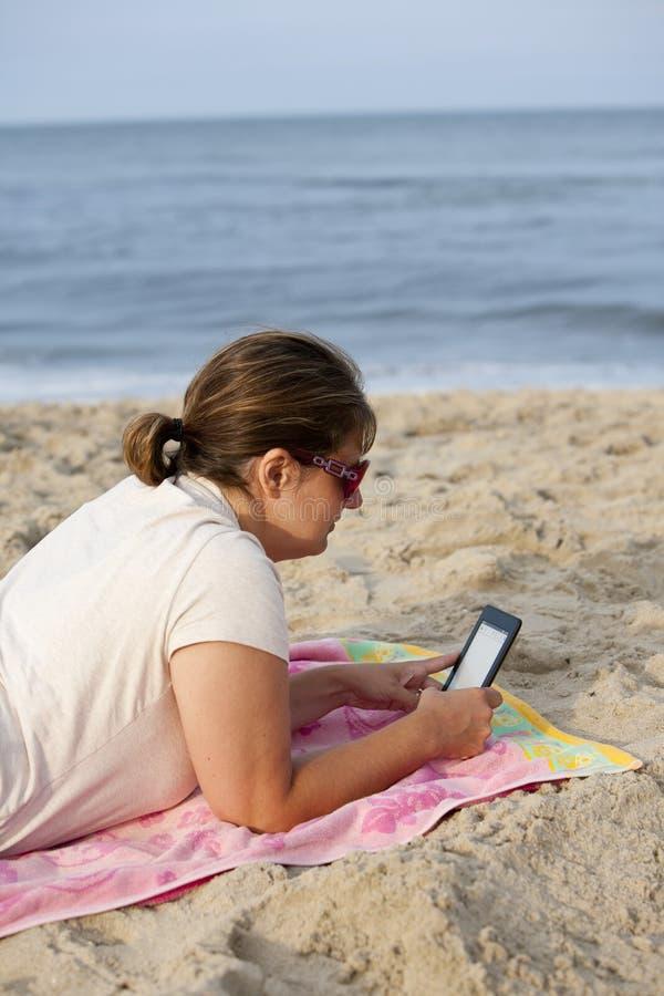 有E读者的妇女在海滩 图库摄影