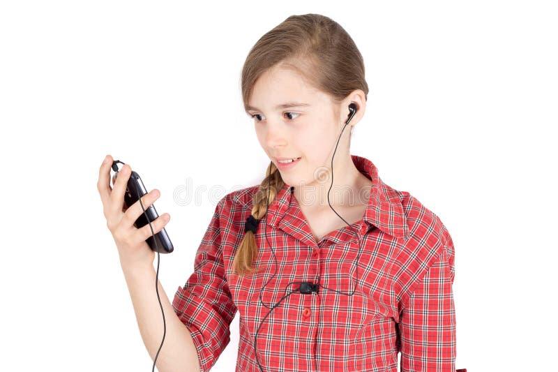 有Earbuds的听到在白色隔绝的她的手机的音乐的微笑的女孩侧视图  免版税库存图片