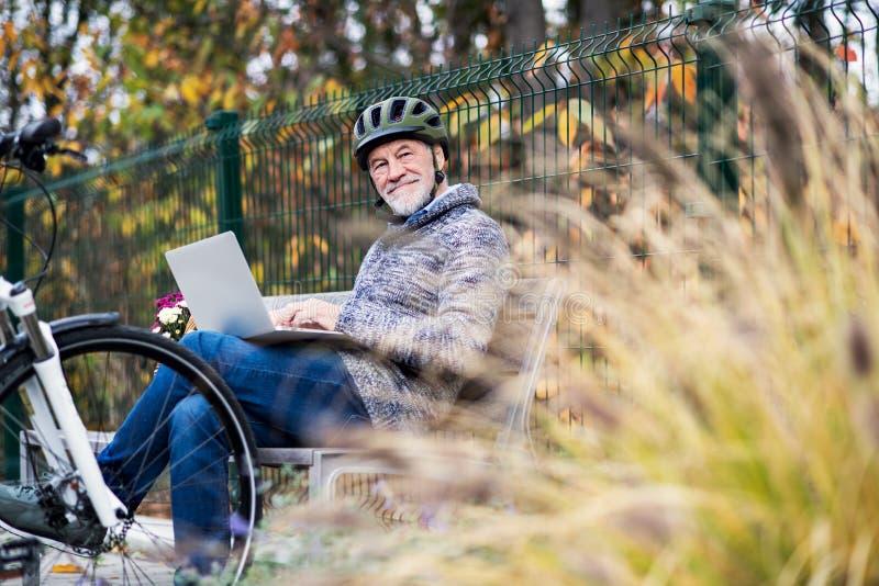 有electrobike的一名老人坐长凳户外在镇里,使用膝上型计算机 库存图片