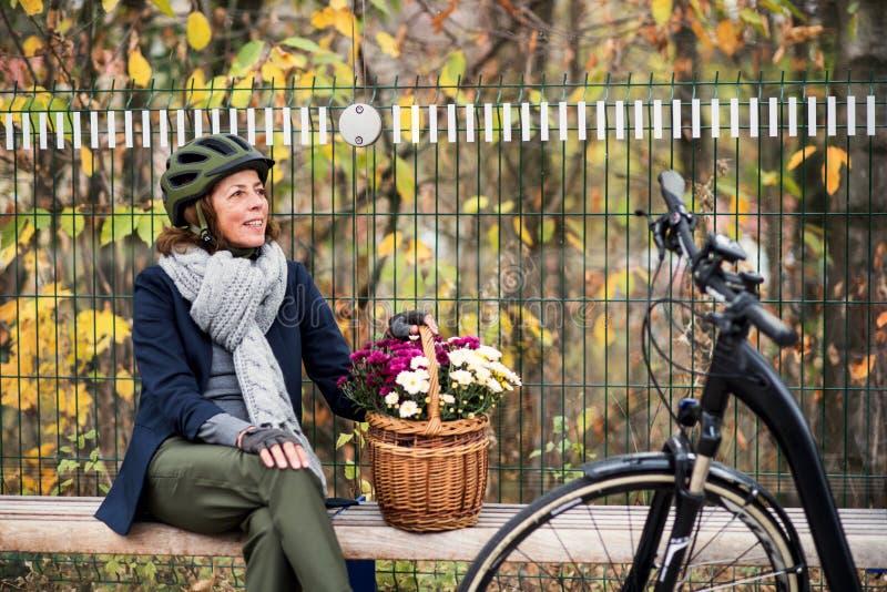 有electrobike的一名资深妇女和花坐长凳户外在镇里 库存照片