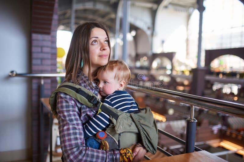 有ergobaby运载的小孩的母亲咖啡馆的 免版税库存图片