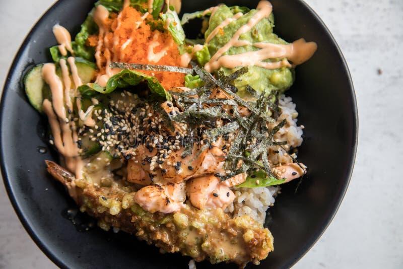 有flambé三文鱼、天麸罗虾、鳄梨调味酱捣碎的鳄梨酱、Masago鱼子酱、沙拉和芝麻的Poké碗在米和黑瓷板材 免版税库存照片