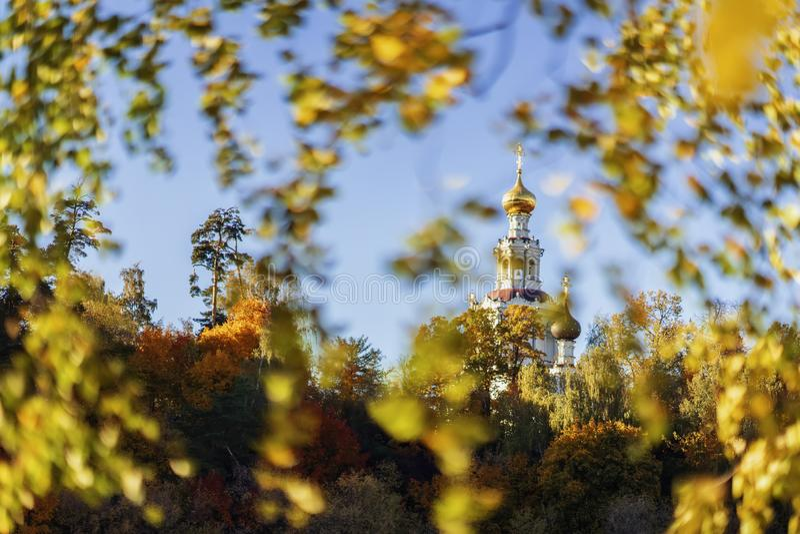 有Golden Dome的白色教会反对蓝天,看法通过秋天黄色离开 免版税图库摄影