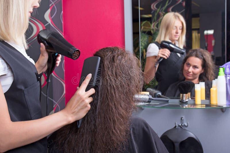有hairdryer的专业烘干fem的美发师和发刷 库存照片