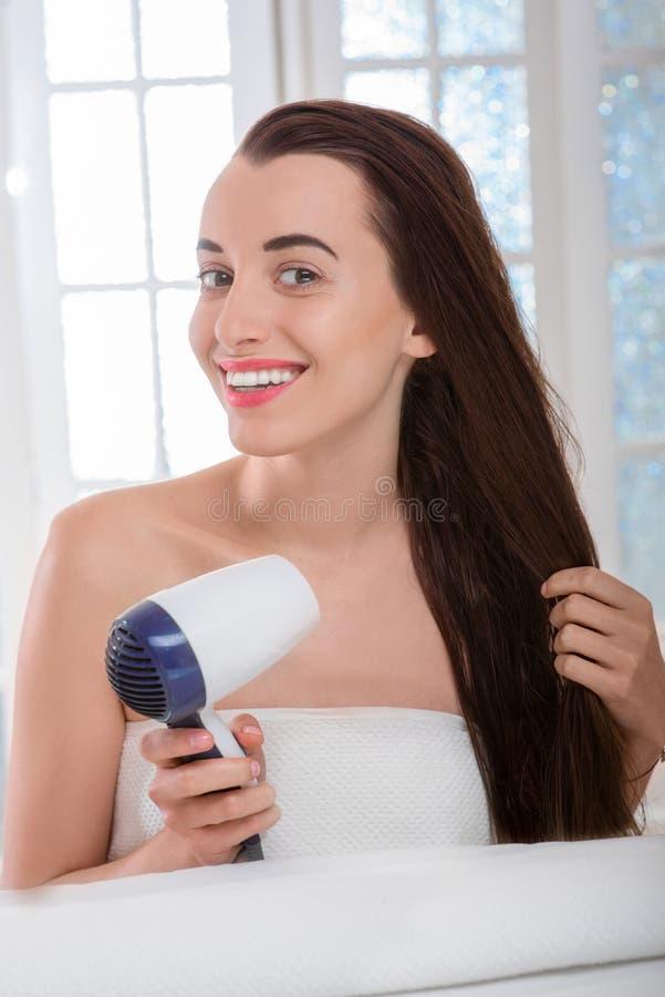 有hairdryer的妇女干毛发 库存照片