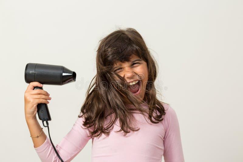 有hairdryer的青少年的女孩 免版税库存图片